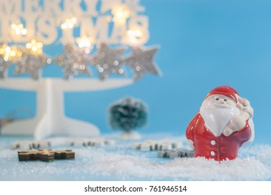 Santa clause doll in red costume hanging a bag ,standing on floor with fault white snow and wood ,blue clear background and bokeh gilter star christmas tree
