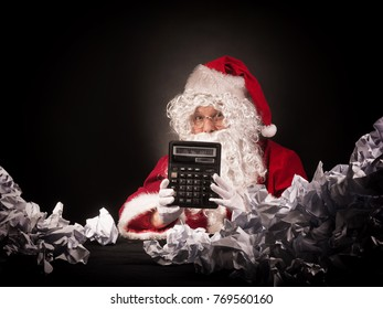 Santa clause with a great heap of crumpled papers. Christmas shopping budget calculation concept.