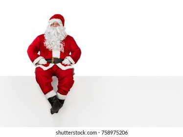 Santa Clause sitting at the edge of a banner isolated on white background with copy space