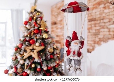 Santa Clause toy on parachute brings gifts at red Christmas tree bokeh background. Big Copyspace concept New Year banner, poster.