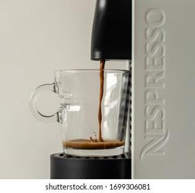 SANTA CRUZ, BOLIVIA - APRIL 05, 2020: Nespresso UMilk white coffee machine, isolated with white background. Closeup view of a machine brewing coffee inside a coffee Nespresso glass cup.