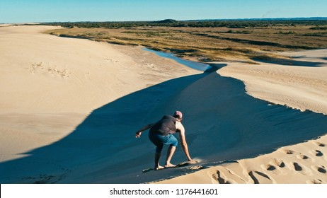 Santa Cruz, Bolivia - SEPT 5 2018: young man sand boarding at the desert sand dunes close to the city