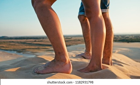 Santa Cruz, Bolivia - SEPT 5 2018: closeup of the legs of a young woman and man enjoying the sunset on the peak of one of the desert sand dune