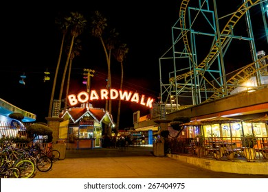 SANTA CRUZ, CA-AUG 2, 2014: Night view of the Santa Cruz Beach Boardwalk, seen  from the front entry with its bright neon sign. The vintage seaside amusement park first opened in 1907.