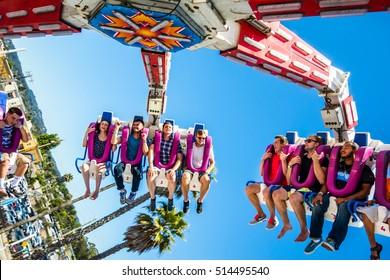 SANTA CRUZ, CALIFORNIA - CIRCA JUNE 2015: Thrill seekers enjoy amusement park rides at an amusement park in Santa Cruz, California.