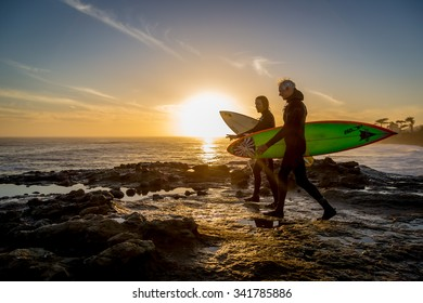 Santa Cruz, California - February 21st 2014 - Two surfers walking with their surfboards with a nice sunset at the background in Santa Cruza, California, USA