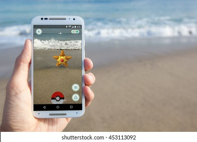 "SANTA CRUZ, CALIFORNIA - July 15, 2016: The hit augmented reality smartphone app ""Pokemon GO"" shows a Pokemon encounter at the beach."
