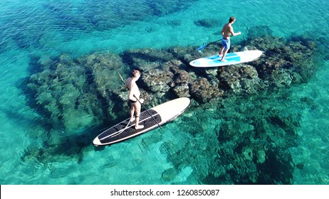 Santa Cruz, California / USA - June 15 2018: Aerial photo of 2 fit men practising SUP or Stand Up Paddle in tropical open ocean bay