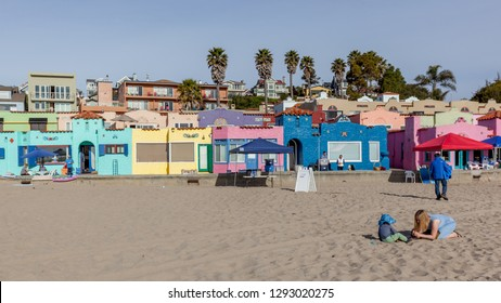 Santa Cruz, California, USA - March 31, 2018: A women and a child on the beach with colorful houses in background  at Capitola Village by the Sea, one of the oldest vacation retreats on Pacific Coast.