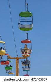 Santa Cruz, CA/USA - April 17, 2016: People enjoy riding the Santa Cruz Boardwalk Skyway (colorful gondola); popular destination in the Monterey Bay area for both tourists and locals alike.