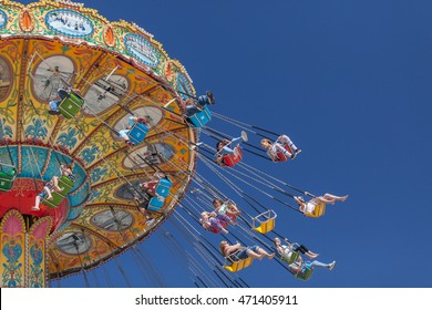 Santa Cruz, CA/USA - April 17, 2016: People enjoy a swinging ride (carousel) at Santa Cruz Boardwalk; popular destination in the Monterey Bay area for both tourists and locals alike.