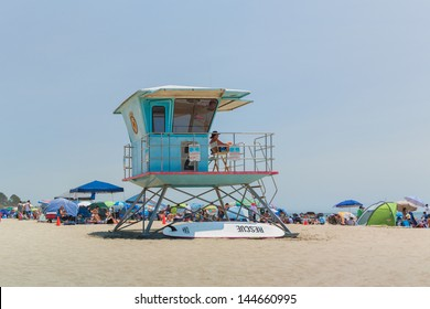 SANTA CRUZ, CA/USA - JUNE 30: An unidentified lifeguard monitors crowded beach activity from a lifeguard tower at Cowell Beach on a in Santa Cruz, California. June 30, 2013