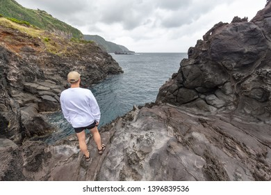 SANTA CRUZ DAS FLORES, PORTUGAL - AUGUST 8: An unidentified tourist explores the dramatic coastline near Santa Cruz Das Flores, Portugal on August 8, 2017.