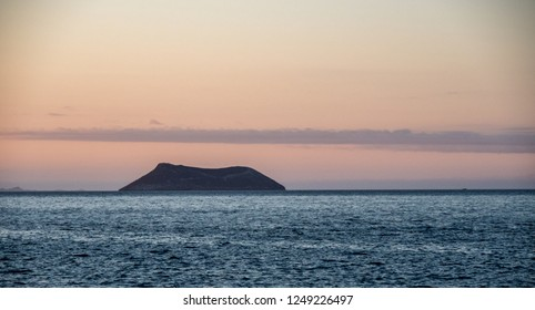 SANTA CRUZ ISLAND, GALAPAGOS - OCT 19, 2018: the characteristic silhouette of the Daphne Major volcanic islet stands out on the horizon, Santa Cruz Island on October 19, 2018.