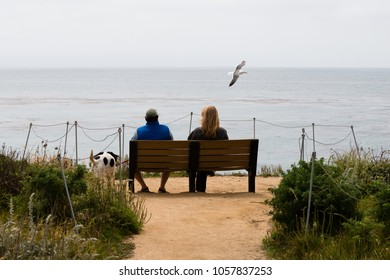 Santa Cruz, USA - May 2, 2015: Couple sitting near the Pacific ocean on the banch