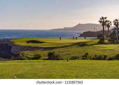 Santa Cruz,Spain,Europe-23/03/2018.Golf players on a green facing the Atlantic Ocean on the island of Tenerife in Spain
