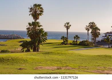 Santa Cruz,Spain,Europe-28/03/2018.Green golf with flag and hole facing Atlantico ocean in Santa Cruz de Tenerife