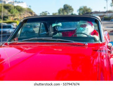 Santa driving his vintage red car.