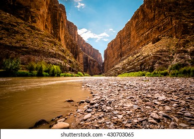 Santa Elena Canyon stands high against a blue sky with the muddy Rio Grande River running through the foreground with Mexico on one side and USA on the other side