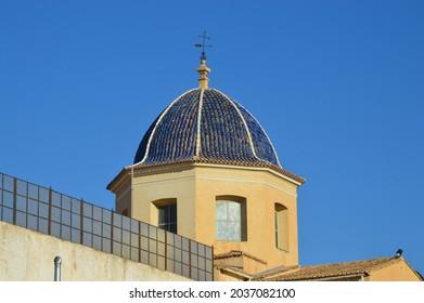 Santa Faz, Alicante, Spain - August 6, 2021: Close up of 17th century blue baroque style pyramid shaped dome steeple of Santa Faz Monastery with a black rod iron weather vane.