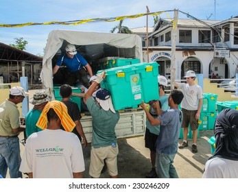 SANTA FE, CEBU, PHILIPPINES - DECEMBER 5th 2013: UK overseas aid workers loading ShelterBox emergency aid onto trucks after Typhoon Haiyan in the Philippines