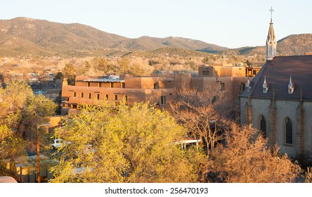 Santa Fe New Mexico at Sunset. The Loretto Chapel is on the right of the photograph. There are trees in the foreground and buildings with the characteristic pueblo architecture in the mid-ground.