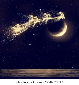 Santa flying on night sky over moon light. Merry Christmas and happy holiday. Elements of this image furnished by NASA