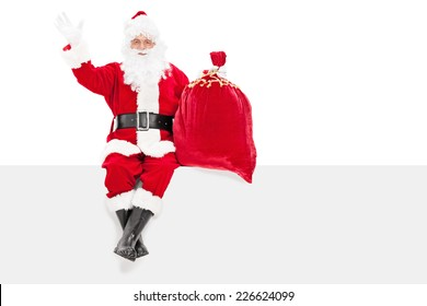 Santa gesturing happiness seated on a panel isolated on white background