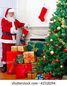 Santa with gifts next to a Christmas tree