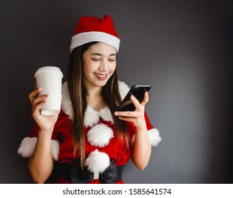 Santa girl holding smartphone and drink hot coffee in Christmas season on gray background.Beautiful woman in santa dress standing with smartphone and takeaway coffee in hands.Social lifestyle.