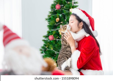 Santa girl kissing her cat with christmas atmosphere. Merry Christmas and New Year's Eve concept.