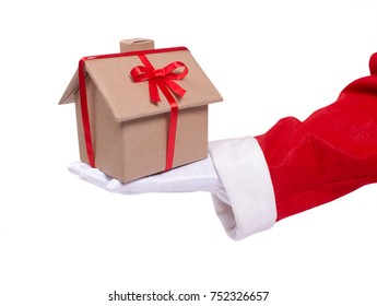 Santa gives as a gift a house. A Santa's hand holds a wrapped house gift with a red ribbon. Present for the New Year. isolated on white