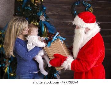Santa gives a gift to mum with baby at christmas evening at home