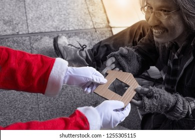 Santa gives house from cardboard to homeless manwith copy space, help the homeless, homeless christmas