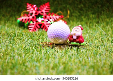 santa and golf ball with snowflake christmas ornament on green grass idea for golfer christmas