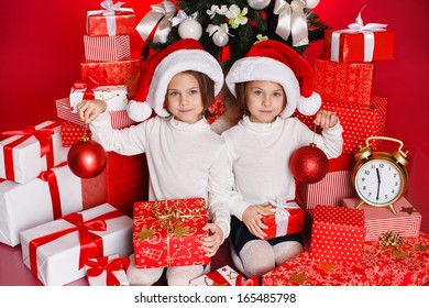 d9ea571066a54 Santa hat Christmas girls holding christmas gifts smiling happy and  excited. Cute beautiful santa children
