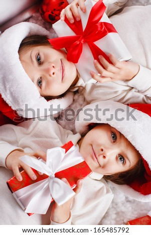 c626400c172b3 Santa hat Christmas girls holding christmas gifts smiling happy and excited.  Cute beautiful santa children