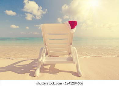 Santa hat hanging on sun lounger, Christmas greeting card concept of winter holidays, nobody