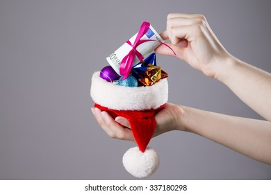 Santa hat with money in woman hands on gray background