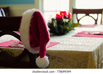 Santa Hat on chair at dinner table with candles in the background blurred