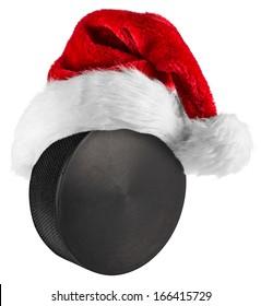 santa hat on ice hockey puck on white background