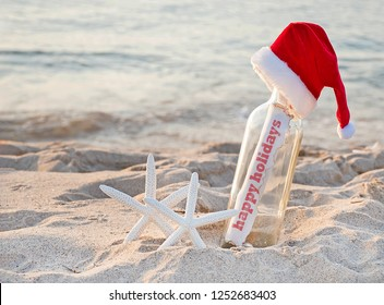 Santa hat on message in a bottle with pair of white starfish in beach sand and Happy Holidays greeting