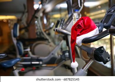 Santa hat on modern fitness machine in gym