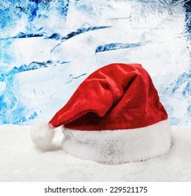 Santa hat on snow on a background of frozen window