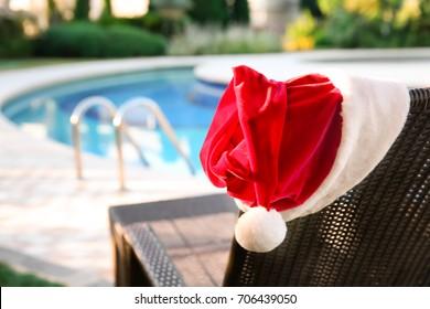 Santa hat on sun lounger near swimming pool at resort. Christmas concept