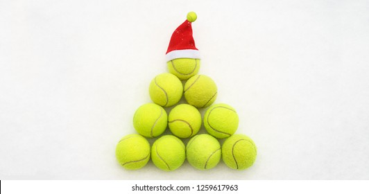 Santa hat on tennis ball on white snow background. Merry Christmas and New year concept with tennis balls. Yellow green color tennis balls in shape fir tree. sport lifestyle. Isolated, horizontal