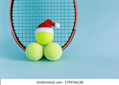 Santa hat on tennis ball and tennis racket on blue background . Merry Christmas and New year concept with tennis balls and racket. sport lifestyle.