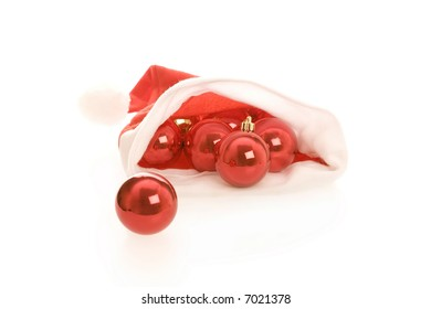Santa hat with red christmas balls isolated on white background. Light shadows under objects