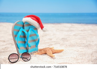 Santa hat with sea star, flip flops and sunglasses on beach. Christmas holidays concept