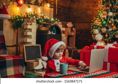 Santa helper baby boy with laptop. Bright New Years interior. Xmas tree. Indoor. Child at Christmas tree and fireplace on Xmas eve. Christmas time. Christmas attributes
